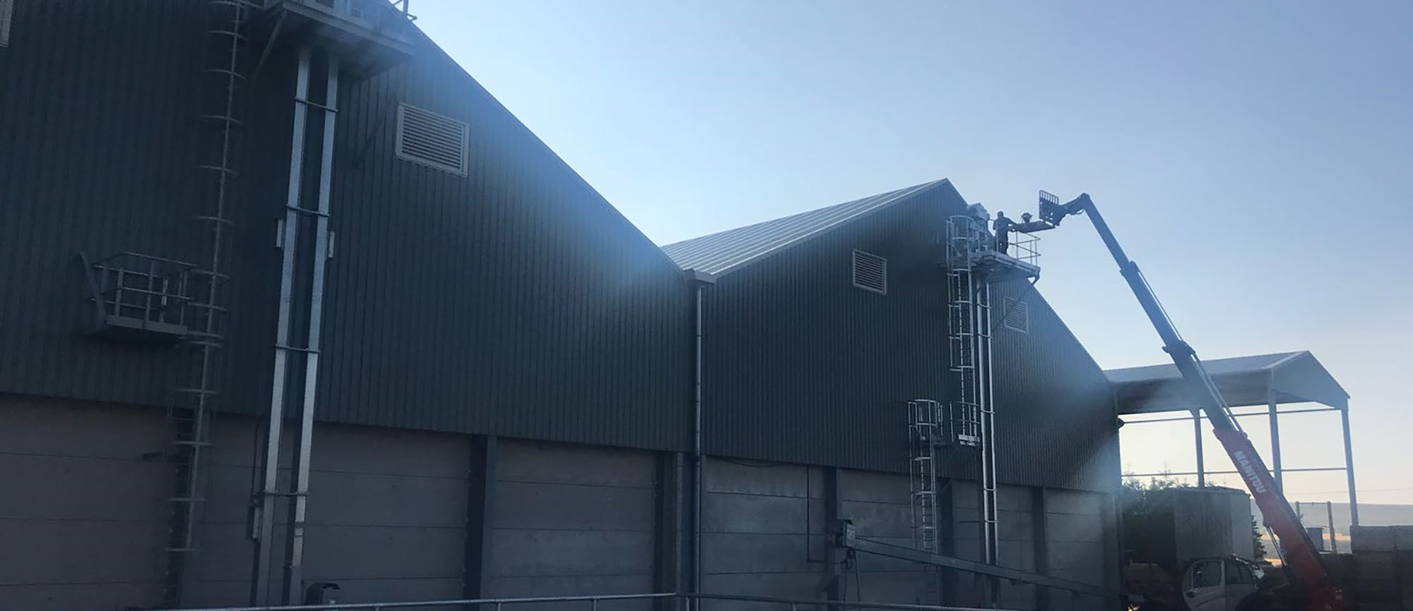 Access ladders, cherry picker and person working at The Bent Farm